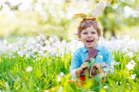 beautiful boy: Cute little kid boy with Easter bunny ears celebrating traditional feast. Happy child  eating chocolate figure on sunny day. Family, holiday, spring , carefree childhood concept.