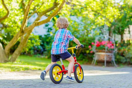 3 4 years: funny blond kid boy in colorful clothes driving bicycle in domestic garden. Toddler child dreaming and having fun on warm summer day. Active games for children outdoors. Stock Photo