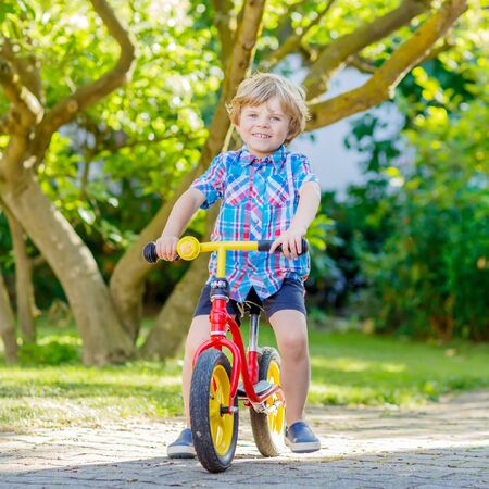 domestic garden: funny blond kid boy in colorful clothes driving bicycle in domestic garden. Toddler child dreaming and having fun on warm summer day. Active games for children outdoors. Stock Photo