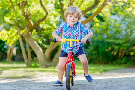 domestic garden: Happy blond kid boy in colorful clothes driving bicycle in domestic garden. Toddler child dreaming and having fun on warm summer day. Active games for children outdoors.