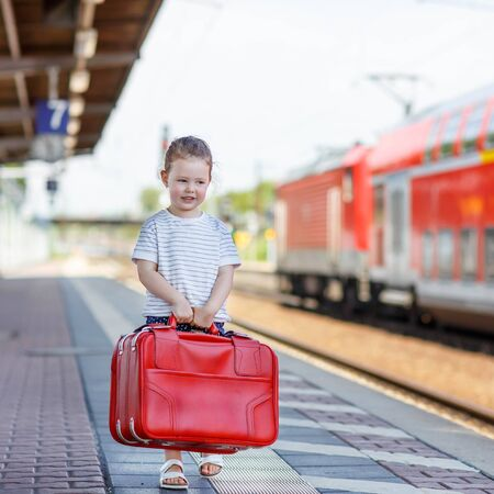 2 3 years: Cute little girl walking with big red suitcase on a railway station. Kid waiting for train and happy about a journey. People, travel, lifestyle concept Stock Photo