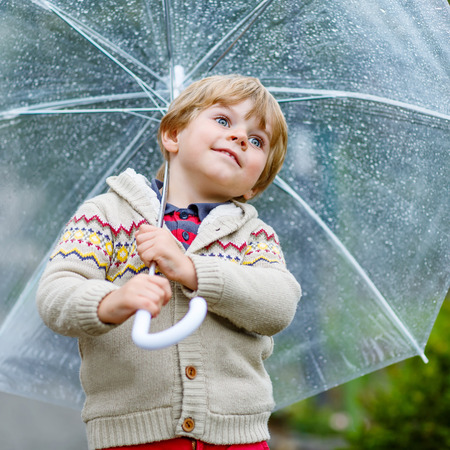 3 4 years: Little blond kid boy walking with big umbrella outdoors on rainy day. Child having fun and wearing colorful waterproof clothes and rain boots. Stock Photo