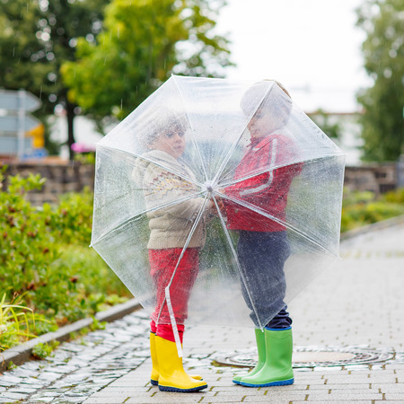 seasonal clothes: Two little children with big umbrella outdoors on rainy day. Kids boys having fun and wearing colorful waterproof clothes and rain boots.
