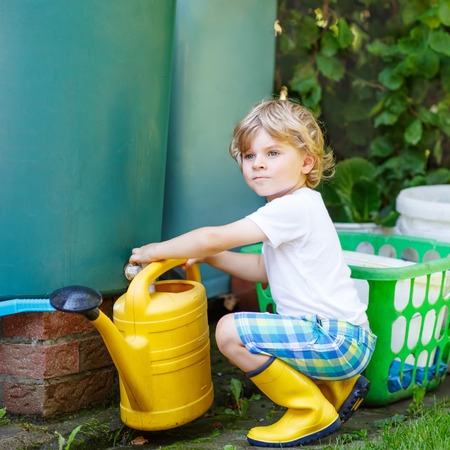 3 5 years: Adorable little kid boy watering plants and vegetables with can in garden. Child helping and having fun on warm summer day. Family, garden, gardening, lifestyle