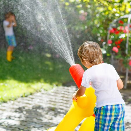 cool kids: Adorable little kid boy and his brother playing together with a garden hose on hot and sunny summer day. Two siblings having fun outdoors. Funny outdoors leisure wth water for children.