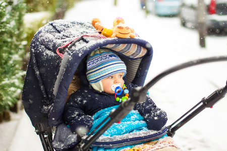 blond boy: Cute baby boy in warm clothes in pram during winter snow fall on cold winter day. Happy carefree childhood. Stock Photo