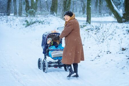 boy lady: Great-grandmother walking with baby boy in pram during snowfall in winter. Happy family. Carefree childhood and generation. Stock Photo