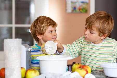 cake mixer: Two little funny brothers baking apple cake in domestic kitchen. Kid boys having fun with working with mixer, eggs and fruits. Children tasting dough