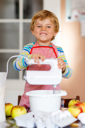 cake mixer: Cute funny blond little kid boy baking apple cake and muffins in domestic kitchen. Happy child having fun with working with mixer, flour, eggs and fruits at home.