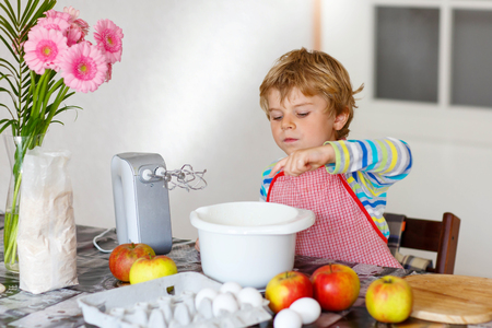 cake mixer: Adorable funny blond little kid boy of four baking apple cake and muffins in domestic kitchen. Happy child having fun with working with mixer, flour, eggs and fruits at home.