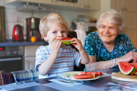 Nettes blondes Kleinkind Junge und seine Urgroßmutter essen Wassermelone in heimischen Küche. Glückliche Familie von kleinen Jungen und pensionierte ältere Frau genießen gesunde Früchte. Standard-Bild