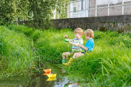 Two little twin boys playing with paper boats by a river on warm and sunny summer day. Active leisure for children. Kid friends having fun together outdoors. Reklamní fotografie