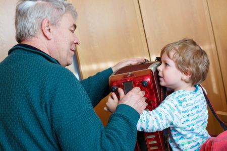 Prodigy: Happy blond dzieciak chłopiec i jego dziadek gra razem z akordeonem. Starszy człowiek uczy wnuka, uroczy maluch grać z instrumentu muzycznego w domu. Zdjęcie Seryjne