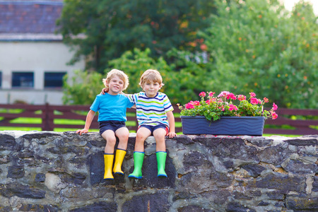 Two funny little kid boys sitting together on stone bridge in european village. Happy family of two. Twins in colorful gumboots, outdoors.