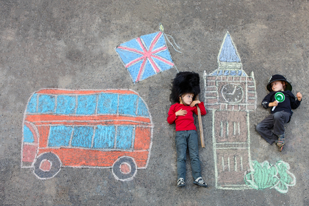 friends having fun: Two funny little friends boys in british queens guard soldier and policeman uniform having fun with London picture drawing with colorful chalks. With Big Ben, Union Jack and red bus. Creative leisure with children. Stock Photo