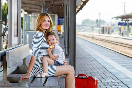 2 3 years: Cute little girl and her mother on a railway station. Kid and woman waiting for train and happy about a journey. People, travel, family, lifestyle concept Stock Photo