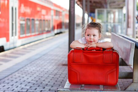 2 3 years: Cute little girl with big red suitcase on a railway station. Kid waiting for train and happy about a journey. Stock Photo