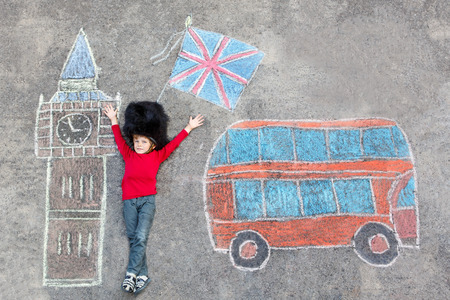 Happy little kid boy in british queens guard soldier uniform having fun with London picture drawing with colorful chalks. With Big Ben, Union Jack and red bus.