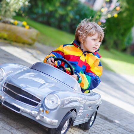 3 4 years: Little preschool boy driving big toy old vintage car and having fun, outdoors. Active leisure with kids outdoors  on warm spring or autumn day. Stock Photo