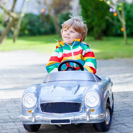 3 4 years: Cute funny boy driving big toy old vintage car and having fun, outdoors. Active leisure with kids outdoors  on warm spring or autumn day. Stock Photo