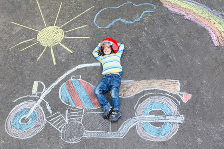 people having fun: Creative leisure for children: Funny little child of four years in helmet having fun with motorcycle picture drawing with colorful chalks. Children, lifestyle, fun concept.