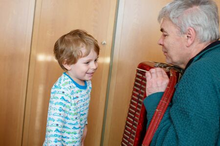harmonist: Happy blond little kid boy and his grandfather playing together with accordion. Senior man teaching his grandson, cute toddler to play with music instrument at home.