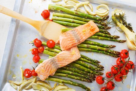 oven tray: Salmon fish and vegetables: green aspargus, cherry tomatoes and fennel, on oven tray Stock Photo