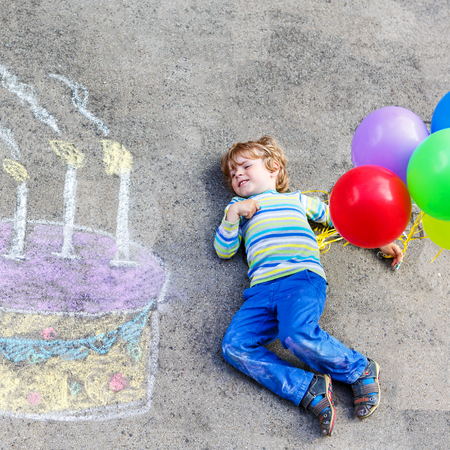 3 4 years: Happy little kid boy having fun with big birthday cake picture drawing with colorful chalks and balloons. Creative leisure for children outdoors in summer. Stock Photo