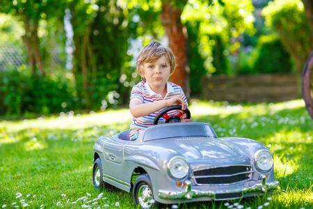 3 4 years: Little preschool kid boy driving big toy old vintage car and having fun, outdoors. Active leisure with children during school holidays on warm summer sunny day. Stock Photo