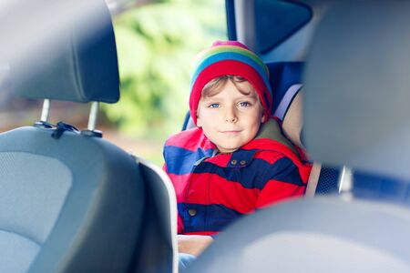 baby 4 5 years: Portrait of preschool kid boy sitting in car. Child in safety car seat with belt. Safe travel with kids and traffic laws concept.