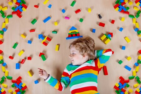 3 4 years: Little blond child playing with lots of colorful wooden blocks indoor. Active kid boy wearing colorful shirt and having fun with building and creating. Stock Photo