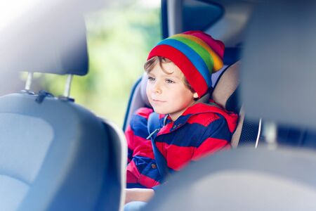 baby 4 5 years: Adorable cute preschool kid boy sitting in car. Child in safety car seat with belt. Safe travel with kids and traffic laws concept. Stock Photo