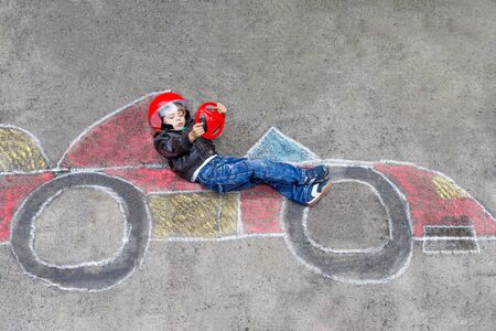 having fun: Funny kid boy having fun with race car picture drawing with colorful chalks. Creative leisure for children outdoors in summer