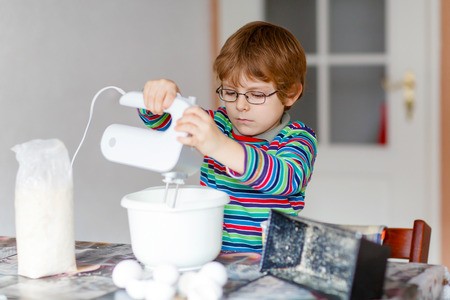 cake mixer: Active funny blond little kid boy n glasses baking apple cake and muffins in domestic kitchen. Happy child having fun with working with mixer, flour, eggs and fruits at home.