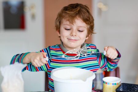 cake mixer: Beautiful funny blond little kid boy baking cake and tasting dough in domestic kitchen. Happy child having fun with working with mixer, flour, eggs and fruits at home.