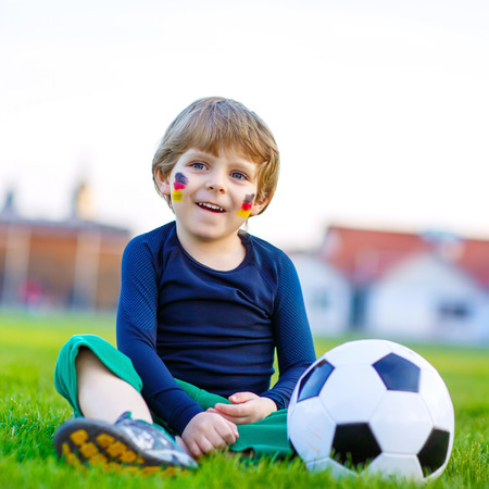 european championship: Adorable little kid boy  having fun with playing soccer with football on field, outdoors. In white German national uniform and painted German flag on face. Happy child about european championship Stock Photo