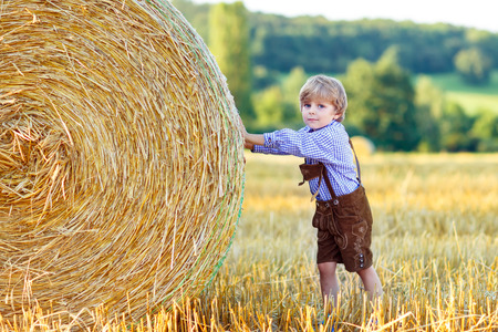 warm shirt: Funny little kid boy in traditional German bavarian clothes, leather shorts and check shirt, walking happily through wheat field near  hay stack or bale. Active outdoors leisure with children on warm summer day.