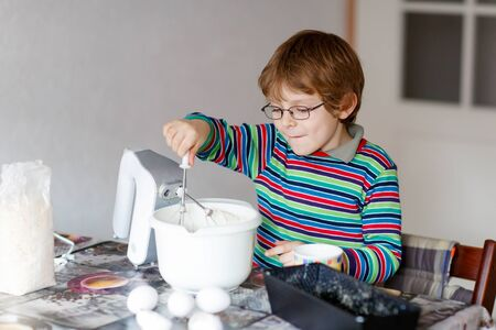 cake mixer: Beautiful funny blond little kid boy n glasses baking cake and tasting dough in domestic kitchen. Happy child having fun with working with mixer, flour, eggs and fruits at home.