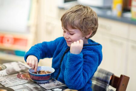 messy kids: Adorable little blond kid boy eating cereals for breakfast or lunch. Healthy eating for children. At nursery or at home. Stock Photo