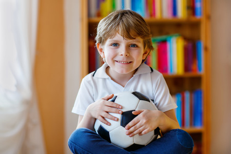 country boy: Little blond preschool kid boy with ball watching soccer european cup game on tv. Funny child fan having fun and cheering winning football team. Champions league concept. Stock Photo
