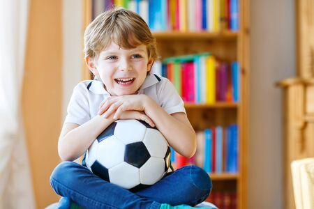 boy ball: Little blond preschool kid boy with ball watching soccer european cup game on tv. Funny child fan having fun and cheering winning football team. Champions league concept. Stock Photo
