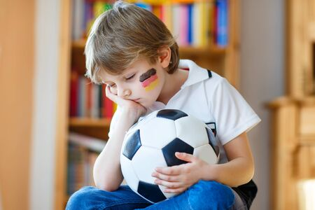 country boy: Little blond preschool kid boy with ball watching soccer european cup game on tv. Sad child about lost game of his football team. Champions league concept.