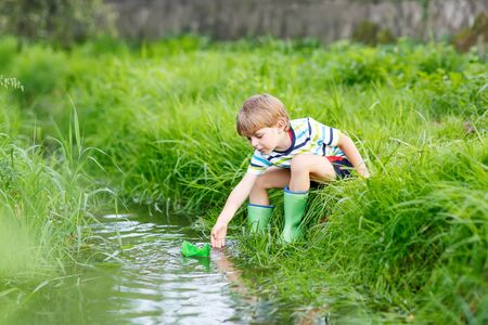 Active little kid boy playing with paper boats by a river on warm and sunny summer day. Active leisure for children. Kid having fun outdoors. Reklamní fotografie