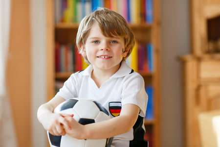 boy ball: Little blond toddler kid boy with ball watching soccer european cup game on tv. Funny child fan having fun and cheering winning football team. Champions league concept. Stock Photo