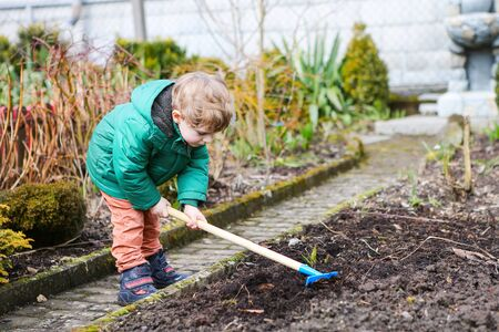 childhood: Little kid boy in spring with garden hoe, planting and gardening, outdoors. Funny toddler having fun with working in garden. Stock Photo