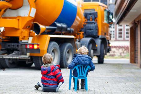 future twin: Two little kid boys having fun with looking on concrete mixer on construction and bulding own house for family.