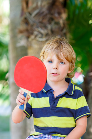 domestic garden: Little cute funny kid boy with table tennis racquet playing in domestic garden. Active outdoors games and leisure for children lifestyle. Stock Photo