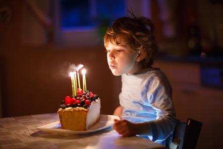 velitas de cumpleaños: de cinco año de edad Adorable niño chico celebrando su cumpleaños y soplando las velas en la torta al horno hecho en casa, de interior. fiesta de cumpleaños para los niños.