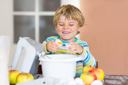 cake mixer: Cute funny blond kid boy baking apple cake in domestic kitchen. Happy child having fun with working with mixer, flour, eggs and fruits.