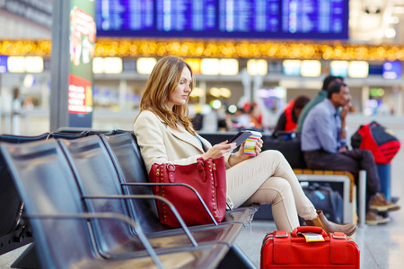 Business woman at international airport reading book and drinking coffee in terminal. Angry passenger waiting. Canceled flight due to pilot strike. Archivio Fotografico